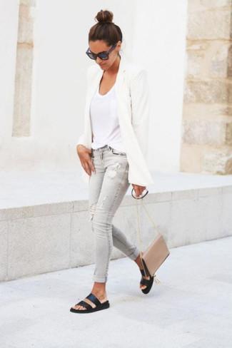 Cómo combinar: sandalias planas de cuero negras, vaqueros pitillo desgastados grises, camiseta con cuello en v blanca, blazer blanco