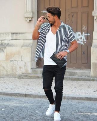 Cómo combinar: tenis de cuero blancos, vaqueros pitillo desgastados negros, camiseta con cuello en v blanca, camisa de manga corta de rayas verticales en negro y blanco
