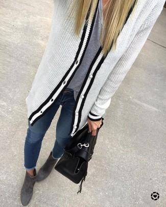 Cómo combinar: botines de ante en gris oscuro, vaqueros pitillo azul marino, camiseta con cuello en v gris, cárdigan de punto en blanco y negro