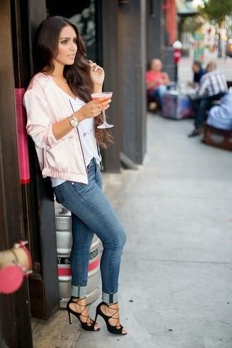 Cómo combinar: sandalias de tacón de ante negras, vaqueros pitillo azules, camiseta con cuello en v estampada blanca, cazadora de aviador de satén rosada