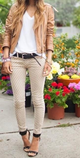 Cómo combinar: sandalias de tacón de cuero negras, vaqueros pitillo a lunares en beige, camiseta con cuello en v blanca, chaqueta motera de cuero marrón claro