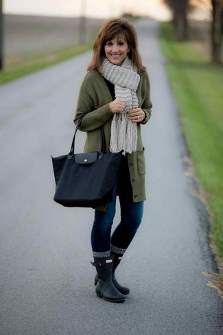 Cómo combinar: botas de lluvia negras, vaqueros pitillo azul marino, camiseta de manga larga negra, cárdigan largo verde oliva