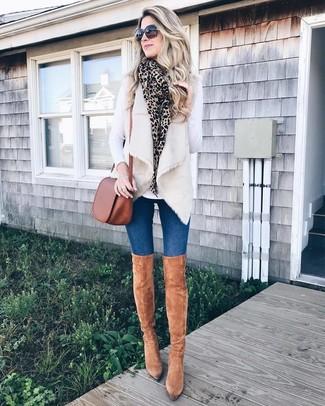 Cómo combinar: botas sobre la rodilla de ante marrón claro, vaqueros pitillo azules, camiseta de manga larga blanca, chaleco de pelo en beige