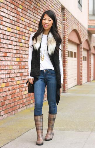 Cómo combinar: botas de lluvia de tartán marrónes, vaqueros pitillo azules, camiseta de manga larga blanca, chaleco de pelo de punto negro