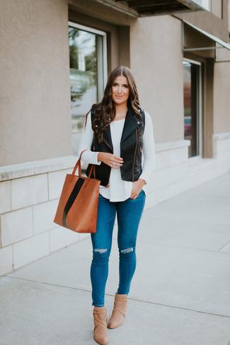 Cómo combinar: botines de cuero marrón claro, vaqueros pitillo desgastados azules, camiseta de manga larga blanca, chaleco de cuero negro