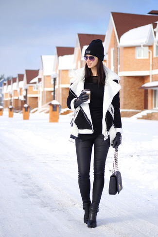 Cómo combinar: botines de cuero negros, vaqueros pitillo de cuero negros, camiseta de manga larga negra, chaqueta de piel de oveja en negro y blanco