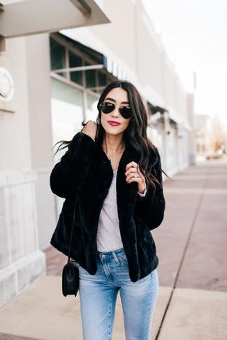 Cómo combinar: bolso bandolera de cuero acolchado negro, vaqueros pitillo celestes, camiseta de manga larga gris, chaqueta de piel negra
