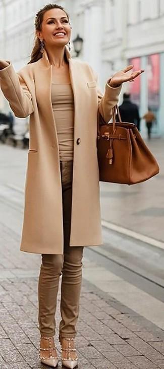 Cómo combinar: zapatos de tacón de cuero con tachuelas en beige, vaqueros pitillo marrónes, camiseta sin manga en beige, abrigo marrón claro