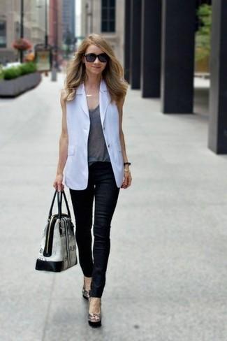 Cómo combinar: zapatos de tacón de cuero negros, vaqueros pitillo de cuero negros, camiseta sin manga gris, blazer sin mangas blanco