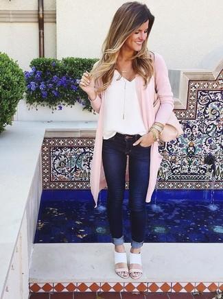 Cómo combinar: sandalias de tacón de cuero blancas, vaqueros pitillo azul marino, camiseta sin manga de seda blanca, cárdigan abierto rosado