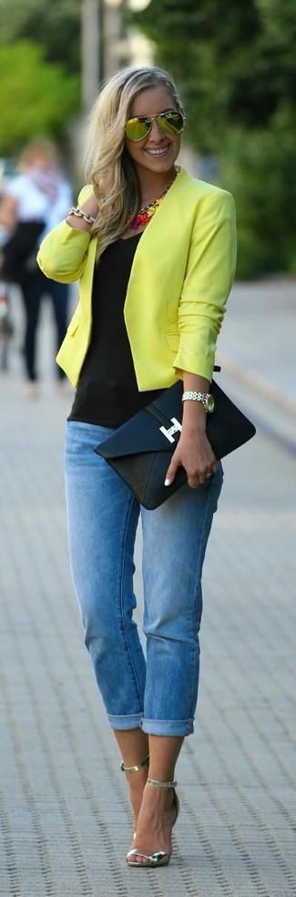 Cómo combinar: sandalias de tacón de cuero doradas, vaqueros pitillo azules, camiseta sin manga negra, chaqueta motera amarilla