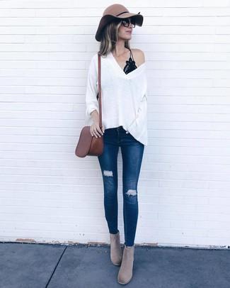 Cómo combinar: botines de ante grises, vaqueros pitillo desgastados azul marino, camiseta sin manga de encaje negra, jersey oversized blanco