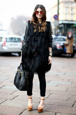 Cómo combinar: sandalias de tacón de cuero gruesas marrón claro, vaqueros pitillo negros, cazadora de aviador de cuero negra, abrigo sin mangas de pelo negro