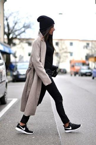 Cómo combinar: deportivas en negro y blanco, vaqueros pitillo desgastados negros, jersey con cuello circular negro, abrigo en beige