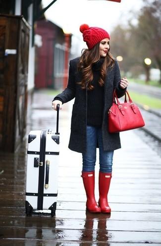 Cómo combinar: botas de lluvia rojas, vaqueros pitillo azules, jersey con cuello circular negro, abrigo en gris oscuro
