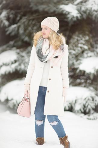Cómo combinar: botas para la nieve de ante marrónes, vaqueros pitillo desgastados azules, jersey con cuello circular en beige, abrigo blanco