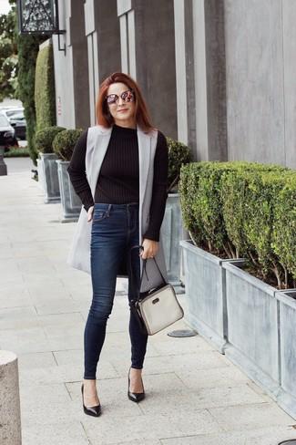 Cómo combinar: zapatos de tacón de cuero negros, vaqueros pitillo azul marino, jersey con cuello circular negro, abrigo sin mangas gris