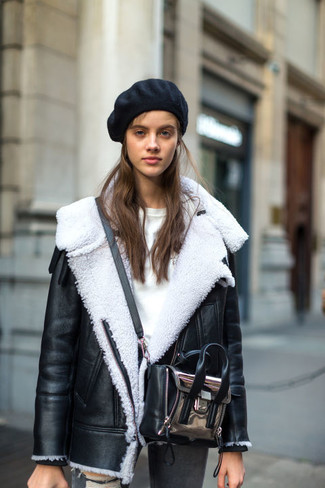 Cómo combinar: bolso bandolera de cuero plateado, vaqueros pitillo desgastados grises, jersey con cuello circular blanco, chaqueta de piel de oveja en negro y blanco