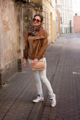 Look de moda: Tenis blancos, Vaqueros pitillo estampados blancos, Jersey con cuello circular de rayas horizontales marrón claro, Chaqueta motera de cuero en tabaco