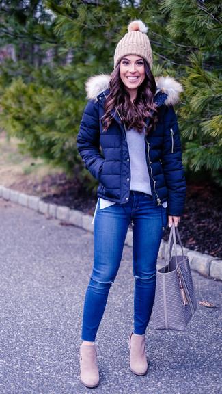 Cómo combinar: botines de ante en beige, vaqueros pitillo desgastados azules, jersey con cuello circular gris, plumífero azul marino