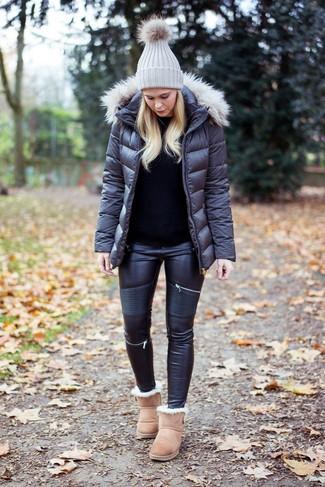 Cómo combinar: botas ugg en beige, vaqueros pitillo de cuero negros, jersey con cuello circular negro, plumífero en gris oscuro