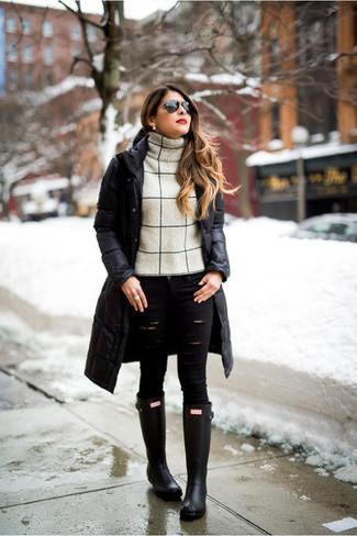 Cómo combinar: botas de lluvia negras, vaqueros pitillo desgastados negros, jersey de cuello alto de lana en beige, abrigo de plumón negro