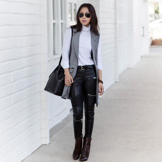 Cómo combinar: botines de cuero en marrón oscuro, vaqueros pitillo de cuero negros, jersey de cuello alto blanco, abrigo sin mangas gris