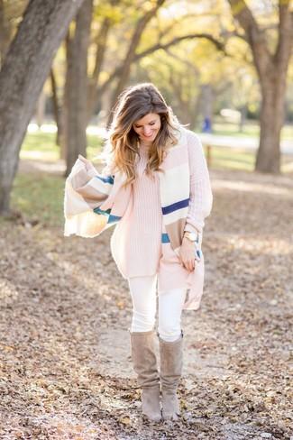 Cómo combinar: botas de caña alta de ante en beige, vaqueros pitillo blancos, jersey de cuello alto de punto rosado, chal de rayas horizontales en multicolor