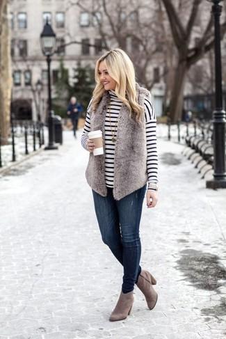 Outfits mujeres: Usa un chaleco de pelo gris y unos vaqueros pitillo azul marino para cualquier sorpresa que haya en el día. Botines de ante grises son una opción atractiva para completar este atuendo.