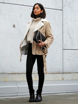 Cómo combinar: botines chelsea de cuero negros, vaqueros pitillo negros, jersey de cuello alto de punto en beige, chaqueta de piel de oveja en beige