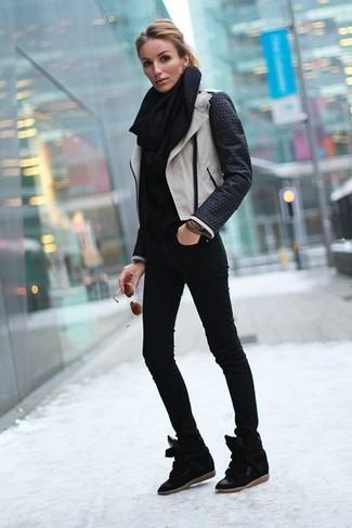 Cómo combinar: zapatillas con cuña de ante negras, vaqueros pitillo negros, jersey de cuello alto negro, chaqueta motera de cuero en negro y blanco