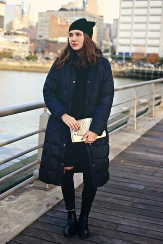 Cómo combinar: botines de cuero negros, vaqueros pitillo desgastados negros, jersey de ochos azul marino, abrigo de plumón azul marino