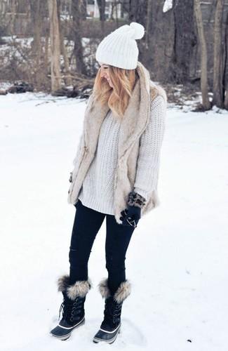 Cómo combinar: botas para la nieve negras, vaqueros pitillo negros, jersey oversized de punto blanco, chaleco de pelo en beige