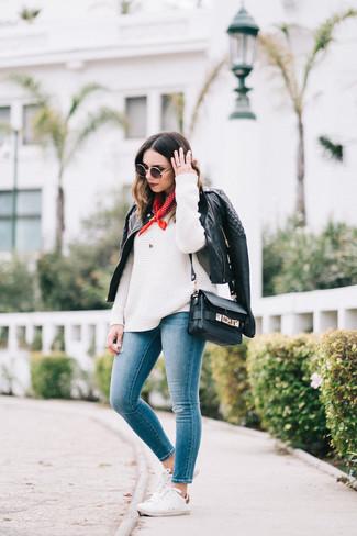 Cómo combinar: tenis blancos, vaqueros pitillo azules, jersey oversized de punto blanco, chaqueta motera de cuero acolchada negra