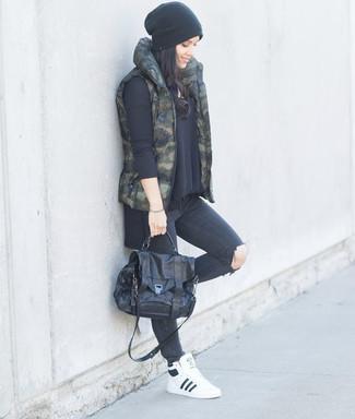 Cómo combinar: zapatillas altas de cuero blancas, vaqueros pitillo desgastados en gris oscuro, jersey oversized negro, chaqueta sin mangas de camuflaje verde oscuro
