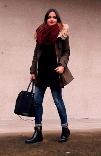 Cómo combinar: botines de cuero negros, vaqueros pitillo azul marino, jersey oversized negro, parka marrón