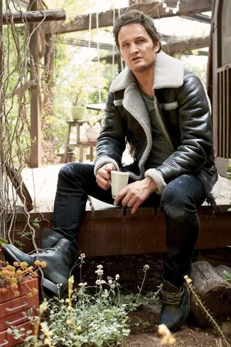 Cómo combinar: botas casual de cuero negras, vaqueros pitillo desgastados negros, camiseta con cuello circular en gris oscuro, chaqueta de piel de oveja negra