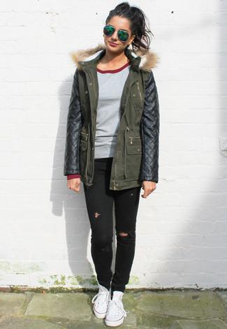 Cómo combinar: zapatillas altas de lona blancas, vaqueros pitillo desgastados negros, jersey con cuello circular gris, parka de cuero verde oscuro