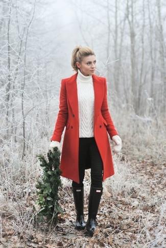 Cómo combinar: botas de lluvia negras, vaqueros pitillo negros, jersey de cuello alto de punto blanco, abrigo rojo