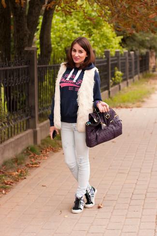 Cómo combinar: zapatillas altas grises, vaqueros pitillo estampados blancos, sudadera con capucha estampada azul marino, chaleco de pelo blanco