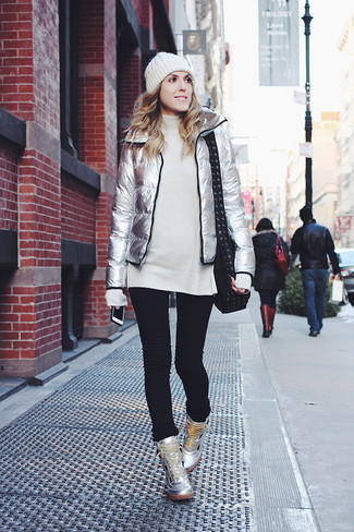 Cómo combinar: zapatillas altas de cuero plateadas, vaqueros pitillo negros, túnica de lana de punto blanca, plumífero plateado