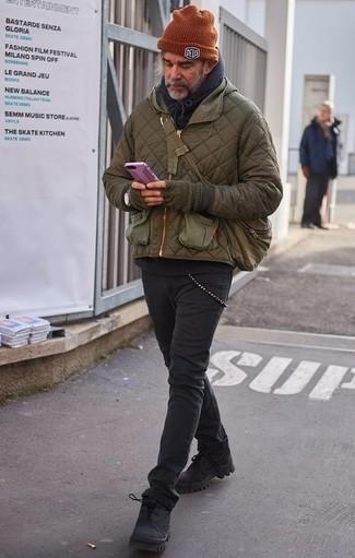 Outfits hombres en clima frío: Si buscas un look en tendencia pero clásico, opta por un plumífero verde oliva y unos vaqueros negros. ¿Quieres elegir un zapato informal? Completa tu atuendo con botas de trabajo de lona negras para el día.