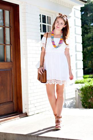 Cómo combinar: vestido con hombros al descubierto de crochet blanco, sandalias con cuña de cuero marrónes, bolso bandolera de cuero marrón, collar con cuentas en multicolor