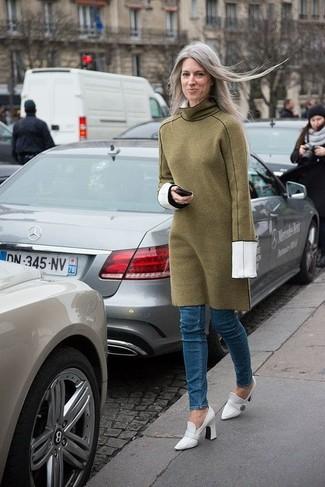 Ponte un vestido jersey verde oliva y unos vaqueros pitillo azules para cualquier sorpresa que haya en el día. Zapatos de tacón de cuero blancos son una forma sencilla de mejorar tu look.