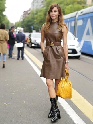 Cómo combinar: vestido recto de cuero marrón, botas a media pierna de cuero negras, mochila con cordón de cuero amarilla, cinturón de cuero marrón