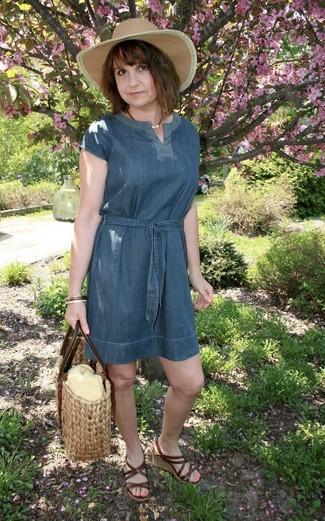 Cómo combinar: vestido recto vaquero azul, sandalias con cuña de cuero en marrón oscuro, bolsa tote de paja en beige, sombrero de paja marrón claro