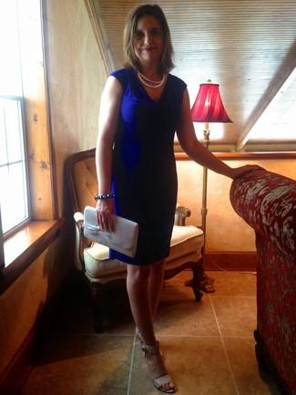 Cómo combinar: vestido tubo azul, sandalias de tacón de cuero en beige, cartera sobre de lentejuelas plateada, collar de perlas blanco
