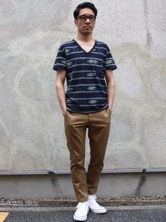 Combinar unas zapatillas altas de lona blancas: Empareja una camiseta con cuello en v estampada azul marino con un pantalón chino marrón claro para un look diario sin parecer demasiado arreglada. Si no quieres vestir totalmente formal, elige un par de zapatillas altas de lona blancas.