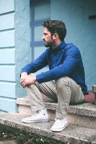 Combinar un pantalón chino en beige: Elige una camisa de vestir azul y un pantalón chino en beige para el after office. Si no quieres vestir totalmente formal, completa tu atuendo con zapatillas altas de lona blancas.