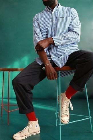 Combinar una camisa de manga larga de rayas verticales en blanco y azul: Elige una camisa de manga larga de rayas verticales en blanco y azul y un pantalón chino negro para lidiar sin esfuerzo con lo que sea que te traiga el día. Si no quieres vestir totalmente formal, elige un par de zapatillas altas de lona marrón claro.